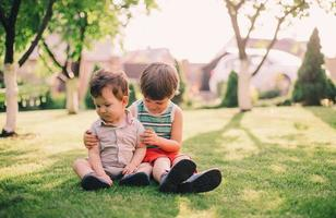 Two brothers sitting together on grass photo