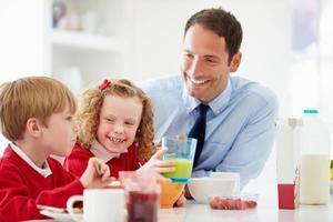 pai e filhos tomando café na cozinha juntos