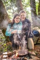 couple cooking on a campfire in the woods photo