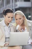 jeunes femmes d'affaires travaillant ensemble sur un ordinateur portable tout en étant assis à l'extérieur