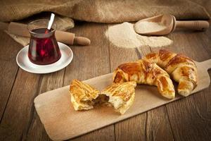 Typical turkish cheese pogaca with wood plate and black tea