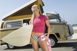 mujer con tabla de surf contra autocaravana