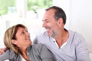 pareja de ancianos hablando juntos en un sofá foto