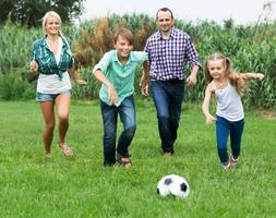 Cheerful family running with ball