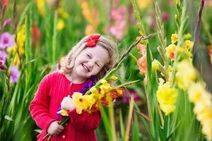 niño recogiendo flores frescas de gladiolos