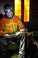 Climber sharpening ice tools outside pod
