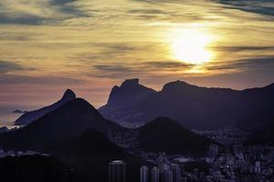 Puesta de sol sobre las montañas en Río de Janeiro, Brasil foto