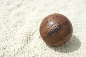 Vintage Brown Football Soccer Ball Sand Beach Background photo