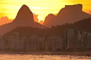 puesta de sol detrás de las montañas en la playa de copacabana foto