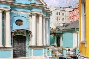 Blue  church with white pillars in middle of colorful houses