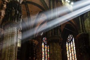 El brillante haz de luz dentro de la catedral de Milán, Italia foto
