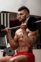 Muscular Men Doing Heavy Weight Exercise For Biceps photo