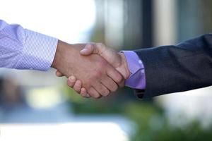 A close-up of two men in suits shaking hands photo