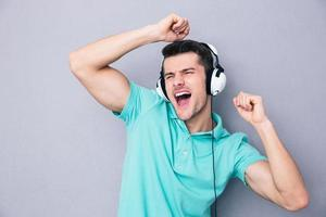Young man singing in headphones photo