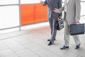 businessmen communicating while walking in railroad station