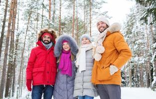grupo de homens e mulheres sorridentes na floresta de inverno