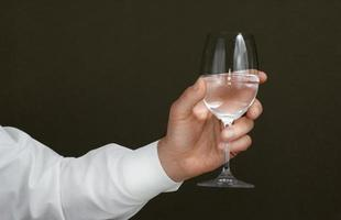 Men's hand with a wineglass of water photo