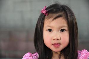 Aziatische vrouwelijke kind in roze jurk
