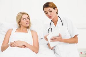 médico explicando informe a paciente femenino
