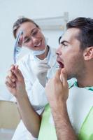 homem olhando no espelho pelo dentista feminino