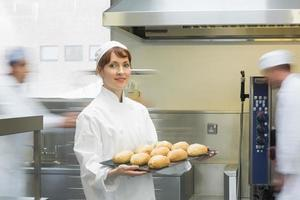 Linda mujer panadero sosteniendo una bandeja para hornear
