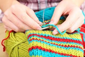 Female hands knitting with spokes close up photo