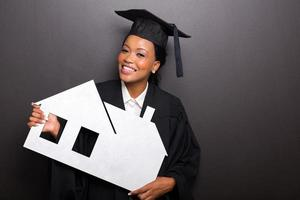 african female university graduate holding paper house