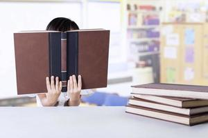 Female little student reads books in class