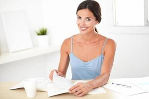 Friendly brunette female sitting and reading books photo