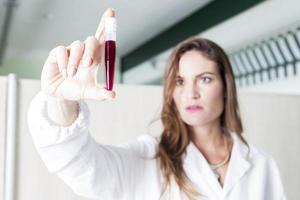 female doctor examines blood tube in laboratory