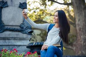 Female student making selfie photo on smartphone
