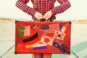 Woman holds suitcase with stamps flags