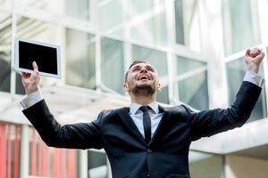 Uspeh.Uverenny businessman rejoices uspehom. Young man raises hi