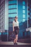 Business woman walking outside in city photo