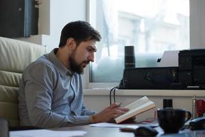 apuesto hombre de negocios planeando su día en la oficina foto
