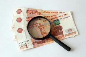 Russian money and magnifying glass photo