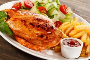 Barbecued chicken fillets, French fries and vegetables on white background