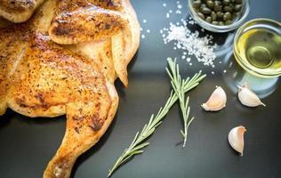 pollo a la parrilla con ingredientes en el fondo de madera oscura foto