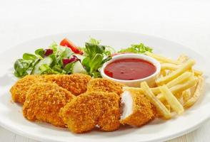 Chicken nuggets chips salad and red sauce on a white plate