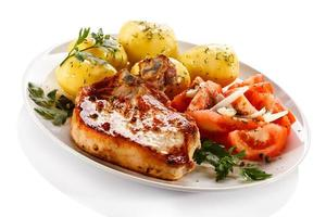 Pork chop, boiled potatoes and vegetables on white background
