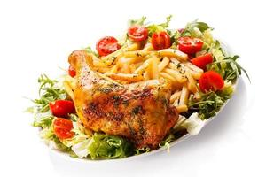 Roasted chicken leg, French fries and vegetables