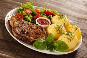 Grilled steak, boiled potatoes and vegetables on wooden background