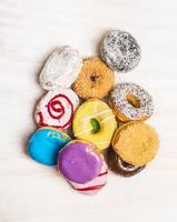 heap of colorful donuts on white wooden background, top view photo