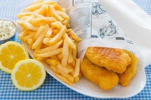 Serving of fish and chips served with lemon