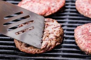 hamburguesa de pattie de carne molida a la parrilla en una espátula contra barbacoa foto