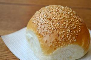 Tasty bun with sesame seeds on wooden table
