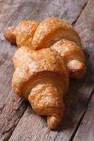 Two tasty fresh croissant closeup vertical