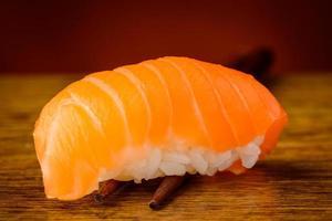 Nigiri sushi with salmon on chopsticks