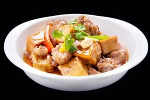 Bean curd cooked pork ribs, isolated on black background photo
