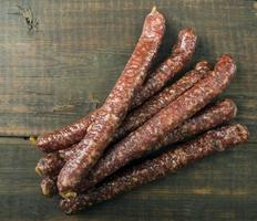 dried sausages on old wooden table